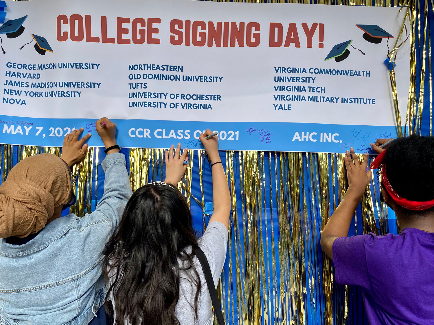 Students affix notes of thanks to the banner at the college-signing ceremony. (Photo by Celia Slater)
